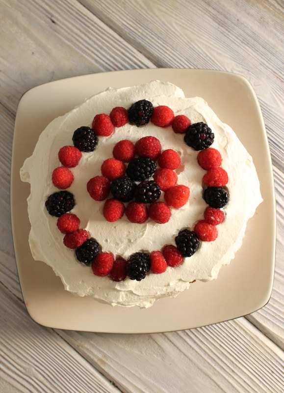 Berries and Cream Layer Cake with berries on top